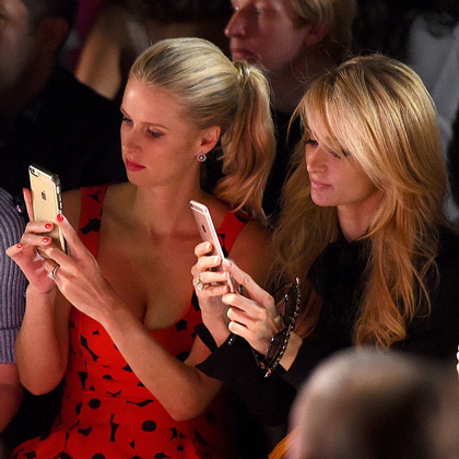 Sisters Nicky and Paris Hilton snapped images on their iPhones from the front row of the Jeremy Scott fashion show.
