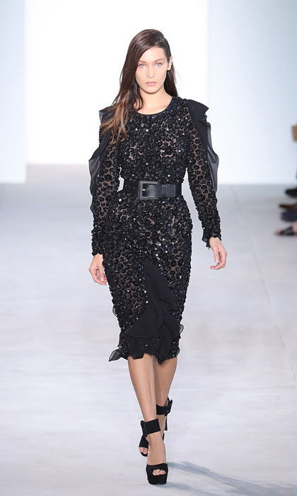 Bella Hadid looked ultra glam modeling an embellished black dress at the Michael Kors show. During the show, the model took a tumble before getting up and continuing down the runway.