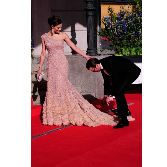 In true gentleman form, Daniel helped Victoria with the train on her dress as they arrived at the Eric Ericcson Hall in June 2010.