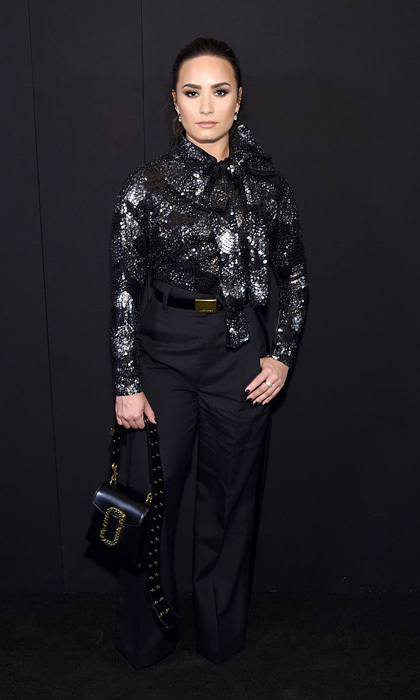 Demi Lovato brought the glamour to Marc Jacobs wearing a dazzling blouse and dark high-waisted trousers.