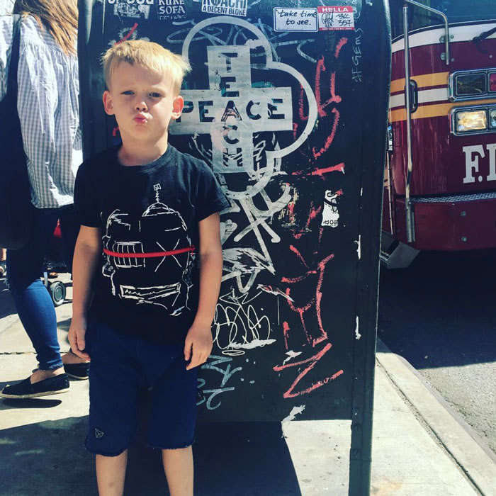 "Peace, love, Luca! Hilary Duff's son Luca Comrie looked cool posing alongside a graffiti mailbox that featured the word ""peace"" on it.