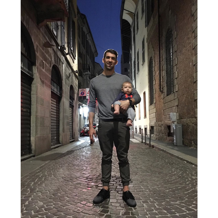 "It was a night on the town for the athlete and his son! Michael shared a photo cradling Boomer on a side street in Italy writing, ""Walking the streets grabbing some food with the fam !! @boomerrphelps @nicole.m.johnson #boomertravels.""