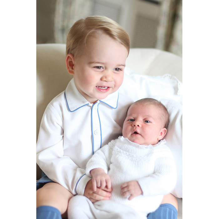 George was one happy older brother sitting perched up with Princess Charlotte in his arms at their family's country home Anmer Hall.