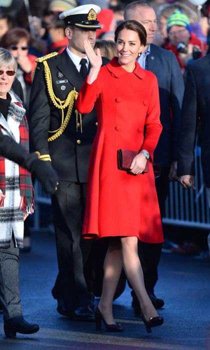 The stylish royal looked sophisticated stepping out in a double breasted scarlet-colored coat dress by Carolina Herrera. The Duchess wore her hair swept up in a low chignon, while accessorizing her look with black pumps and drops earrings. 