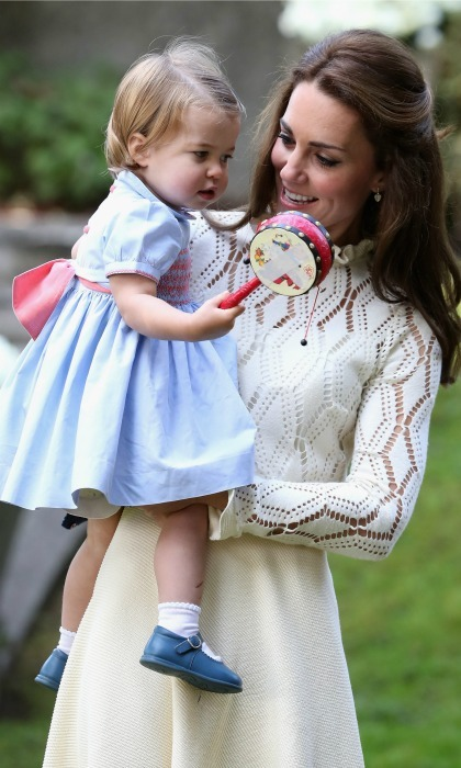 Charlotte played with a toy in her mother's arms during her first official engagement in Canada. 