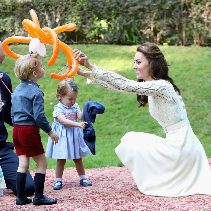 Kate played with George and his balloon, placing it on his head, at a children's party during their royal tour of Canada.