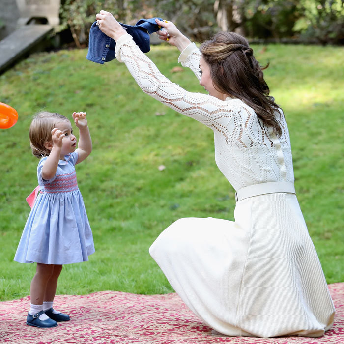 Kate gave daughter Princess Charlotte a hand removing her navy button down cardigan.