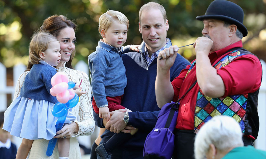 Kate held on to Charlotte as the royal family watched an entertainer blow a balloon for Prince George.