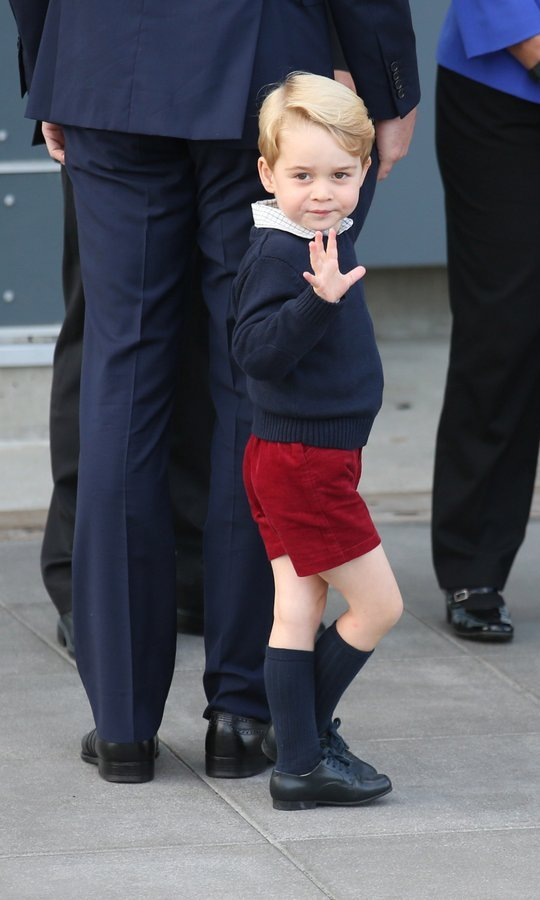 The little Prince looked adorable in red burgundy shorts with a navy blue sweater, with his blonde hair swept to one side.