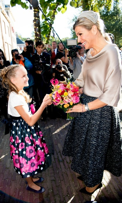Queen Maxima was greeted by an equally stylish young spectator as she arrived at the Het Loo Palace Museum in Apeldoorn, Netherlands.