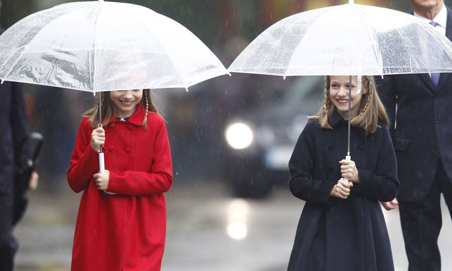 Princesses Sofia and Leonor kept dry from the rain, toting umbrellas to the parade in Madrid.
