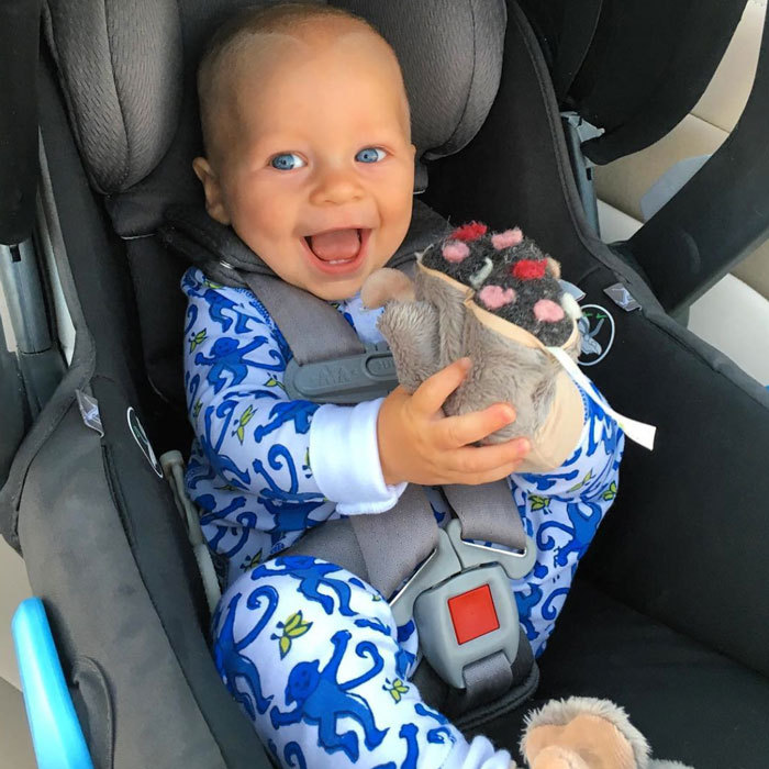 "Seth Meyers' son Ashe was as cute as a button, flashing a bright smile from his car seat as he snacked on his slippers before ""hitting the road.""