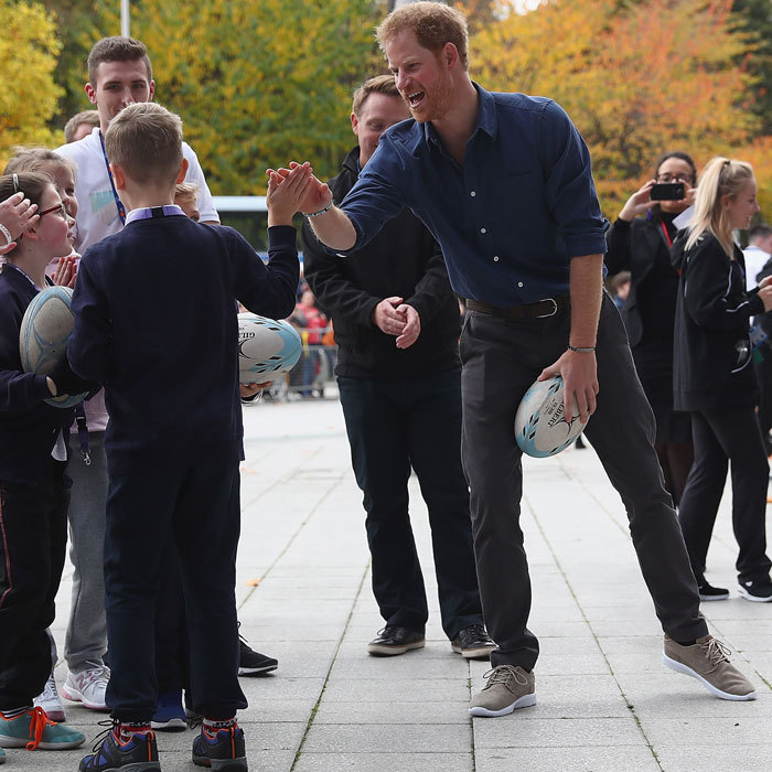 Oh yeah! Harry gave a high-five to a young boy, while participating in a rugby game.