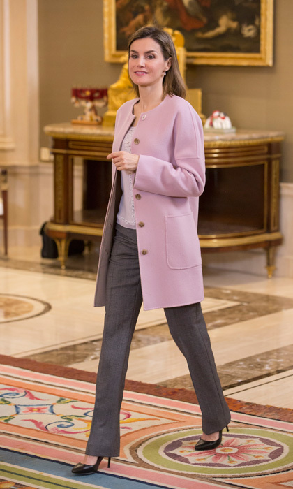 King Felipe's wife added a splay of color to her grey pants with a soft pink BOSS Hugo Boss cashmere cocoon coat.   for an official meeting at Zarzuela Palace.