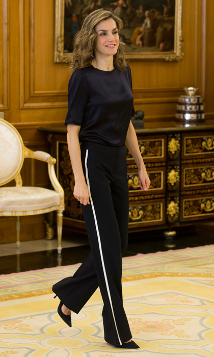 Queen Letizia donned contemporary dark blue trousers that featured side contrast stripes by BOSS, which she paired with a relaxed Mango blouse to attend audiences at Zarzuela Palace in October 2016.