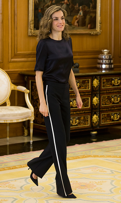 Queen Letizia channeled sports luxe in black tailored trousers with white stripe detail.