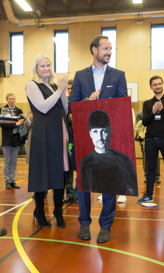 Crown Princess Mette-Marit of Norway applauded as her husband Crown Prince Haakon received a portrait of himself at the Groenland adult education center in Oslo prison.