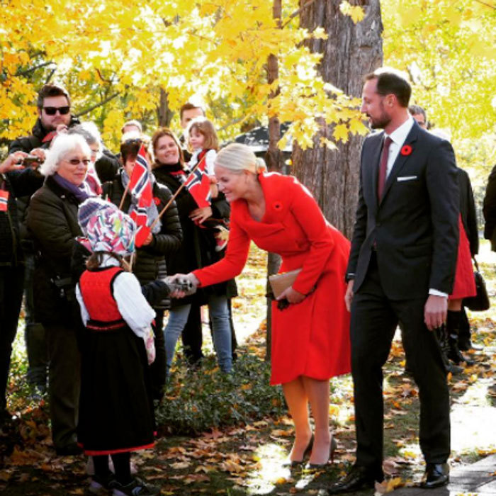 Crown Princess Mette-Marit looked lovely in red as she greeted children from Ottawa during her royal tour of Canada.