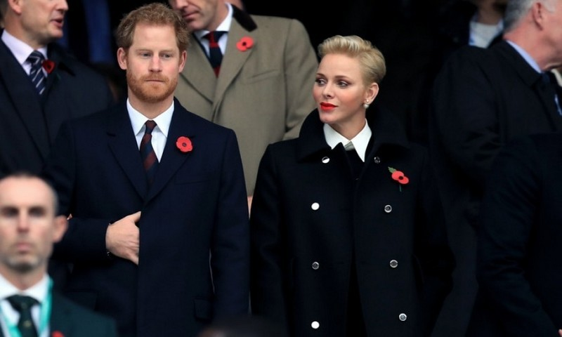 Though some were expecting to see Prince Harry's girlfriend Meghan Markle by his side during the England vs. South Africa rugby match at Twickenham, he was instead joined by Monaco's Princess Charlene. The two cheered on while wearing poppy pins to remember the soldiers who lost their lives in battle. 