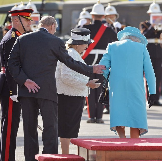 In Malta in November 2015, Prince Philip gallantly helps the Queen step down from a platform as she prepares to inspect a Guard of Honor at Luqa airport.