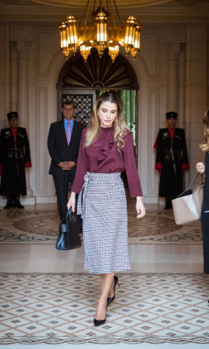 Queen Rania looked stylish in a gingham pencil skirt with a marroon ruched blouse for some meetings at the Royal Hashemite Court.