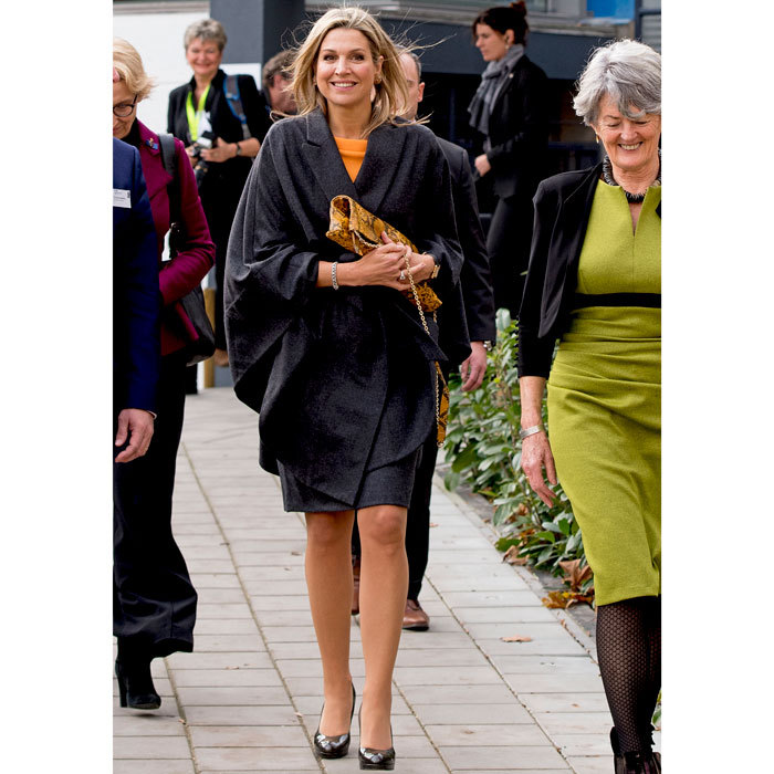Queen Maxima of Netherlands looked cozy donning a grey wrap wrap poncho over her vibrant knit top and pencil skirt for an outing to Thomas More College in Rotterdam, where she talked about the development of music education. 