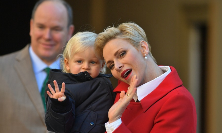 Princess Charlene held on to Prince Jacques as he wavesd to the crowd during the annual Christmas gifts distribution at the Monaco palace. 