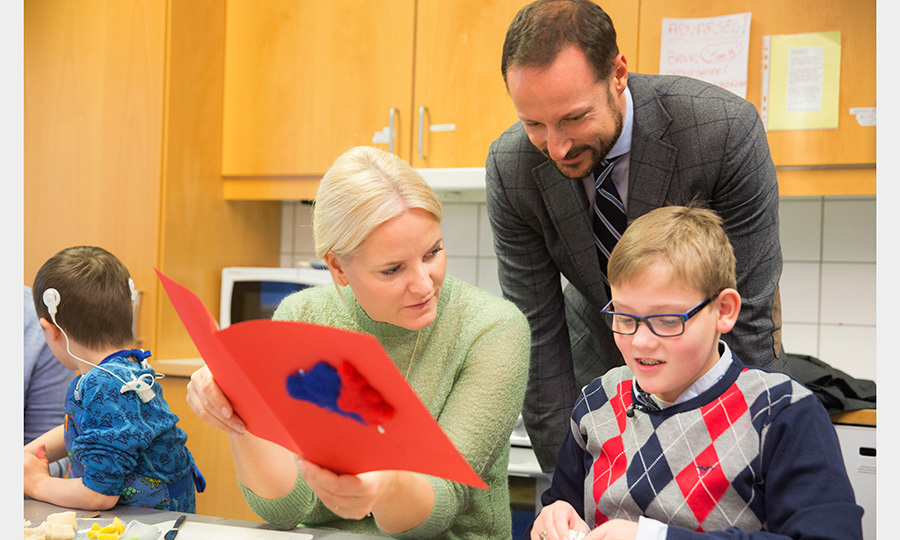 Crown Prince Haakon and Crown Princess Mette-Marit of Norway read a book with young Sander Rognlien Pettersen during a  visit to Haug school and resource center in Bærum. 