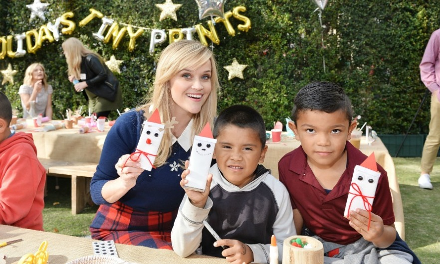 December 12: Reese Witherspoon showed off her artwork next to some lucky kids during the Tiny Prints Presents The Baby2Baby Snow Day at The Grove in L.A. 