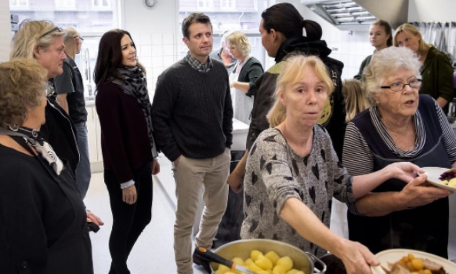 "Crown Princes Mary and Crown Prince Frederik paid a visit to the ""Café for the Homeless"" in Copenhagen, where they toured the facility and greeted volunteers.
