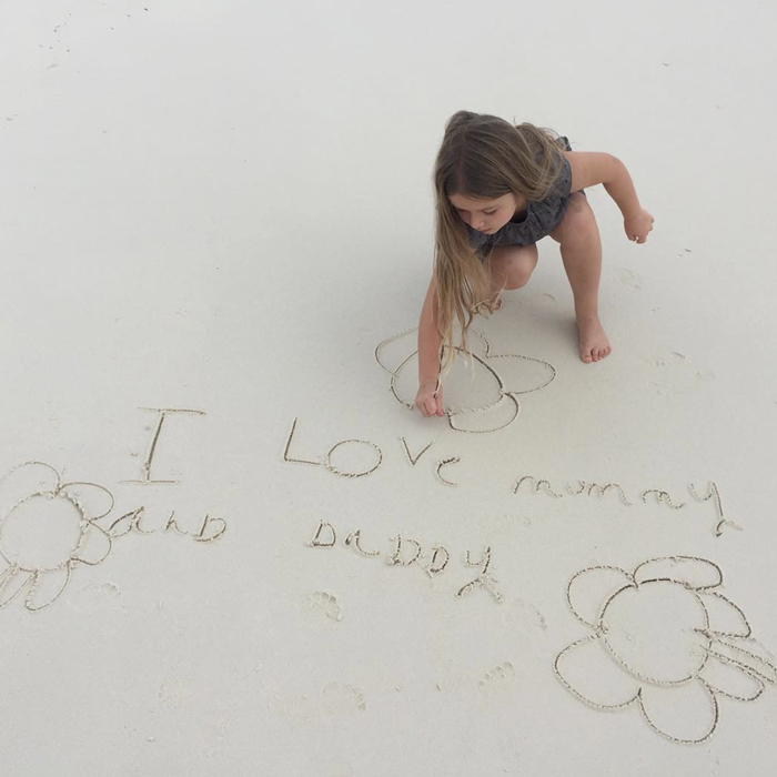 "Harper Beckham took time out of her holiday vacation in the Maldives to pen a sweet love note to her parents, David and Victoria Beckham, which read:, ""I love mummy and daddy."" Victoria captured her daughter writing the message in the sand. Attached to the photo, the fashion designer wrote, ""Kisses from my baby girl  X VB.""