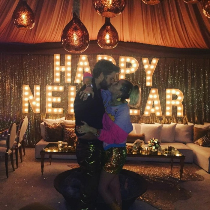 New Year's kiss! Miley Cyrus and Liam Hemsworth locked lips at what appeared to be a mixed family New Year's Eve party. Members of both the Cyrus and Hemsworth clan seemed to be in attendance.
