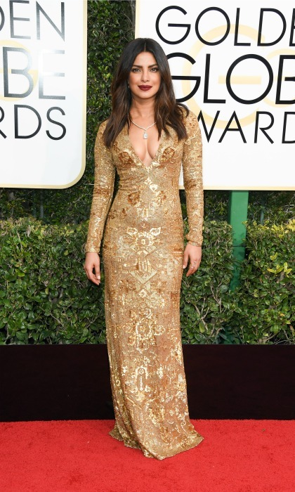 Priyanka Chopra turned heads in a plunging, gold gown y Ralph Lauren.