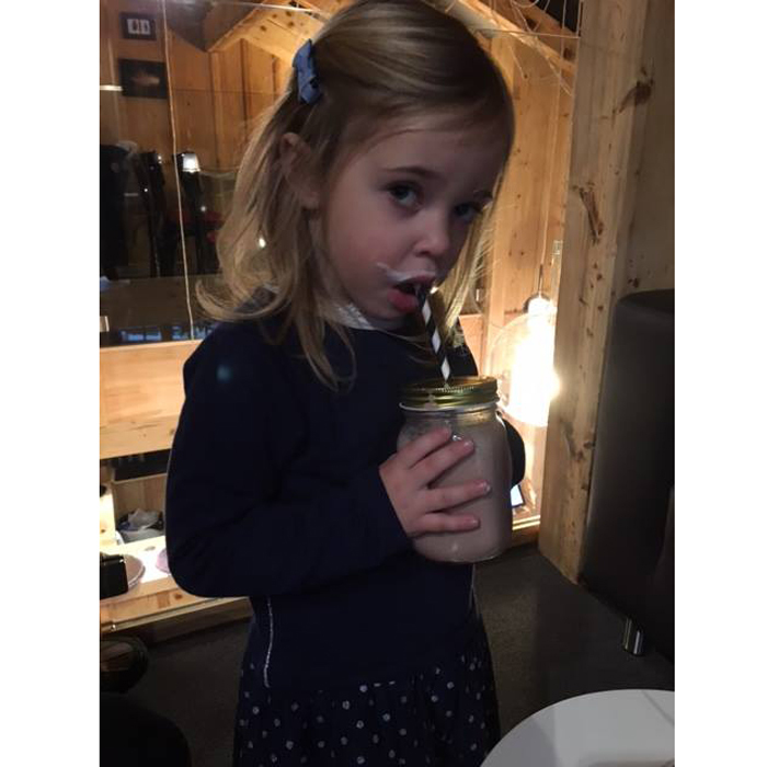 The Swedish tot snacked on a chocolatey drink during a ski vacation in Switzerland with her parents and grandparents.