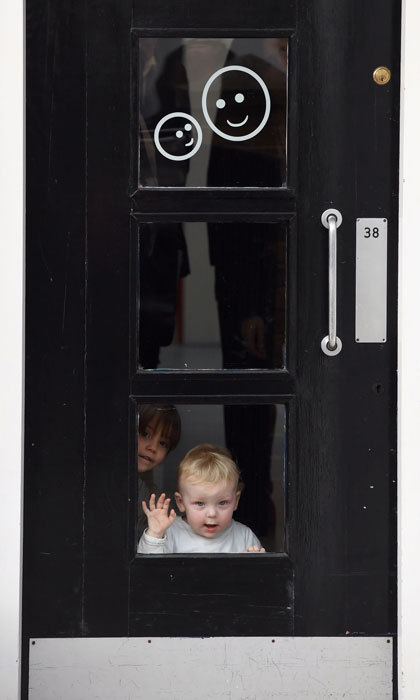 Two young children adorably peered through a window during the Duchess's visit to Anna Freud National Centre for Children and Families.  