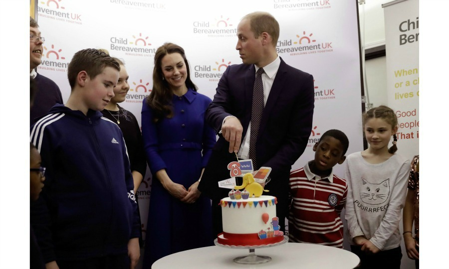 Prince William and Duchess Kate (along with the kids around) couldn't wait to dig into the confection during their visit to the Child Bereavement UK Centre in London. 