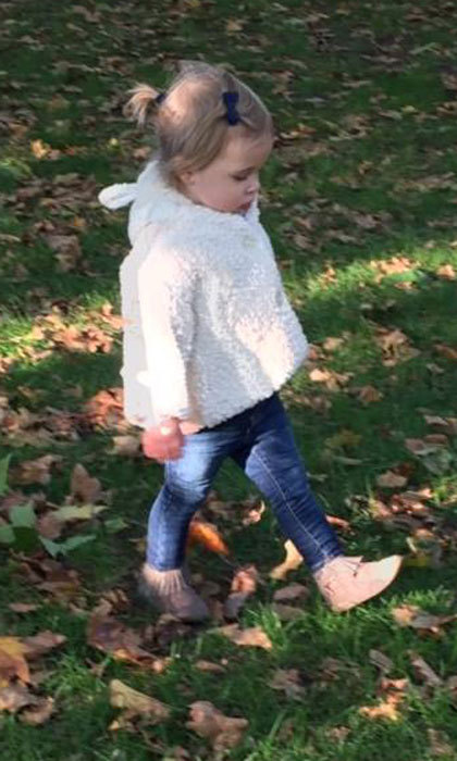 The Swedish tot was dressed for fall as she went for a walk in the park.