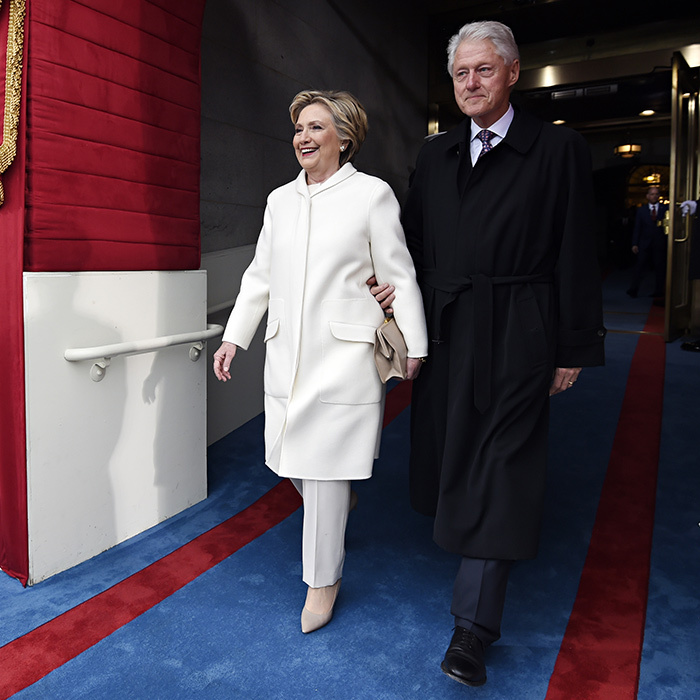Former two-term President Bill Clinton escorted wife Hillary Clinton, who opted for her signature look – a pantsuit – in winter white.