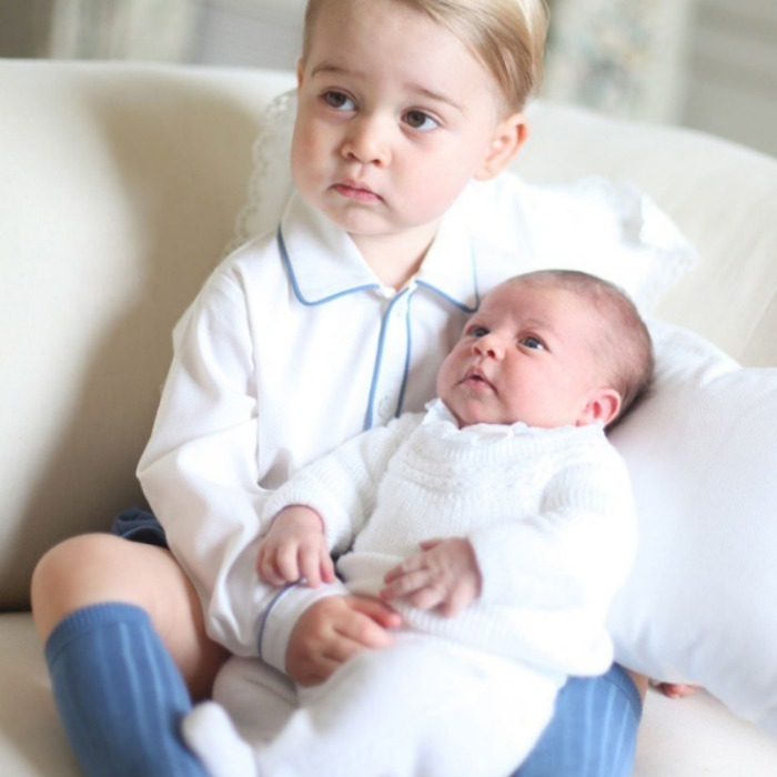 Kate Middleton snapped this photo of Prince George holding on to his new baby sister Princess Charlotte inside of their home. 