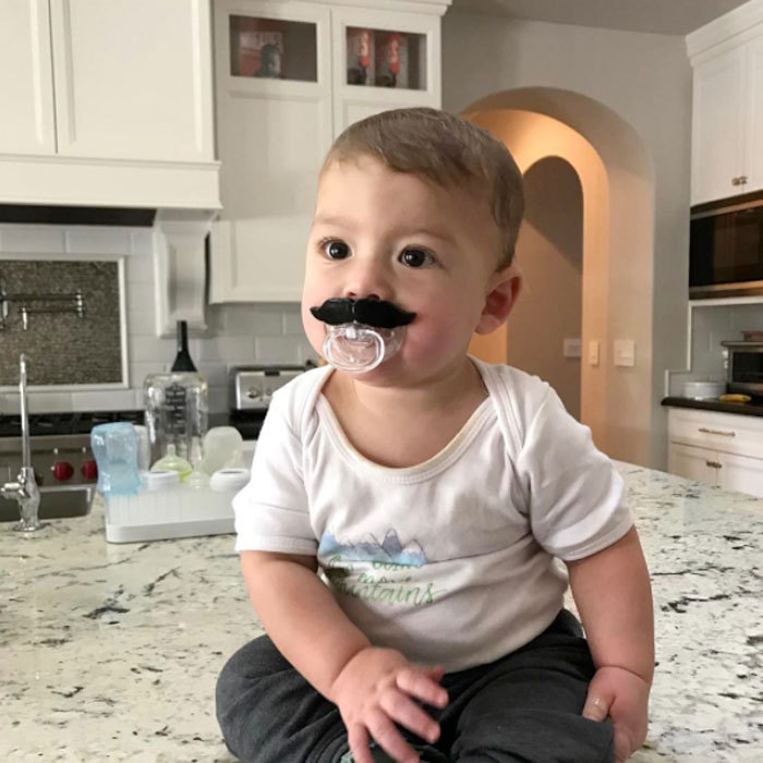 "Boomer Phelps was rocking a new look on his Instagram! The adorable son of Micheal Phelps posed for a photo wearing a silly pacifier on a kitchen counter. Attached to the picture, a message read: ""I love my new mustache!!!""