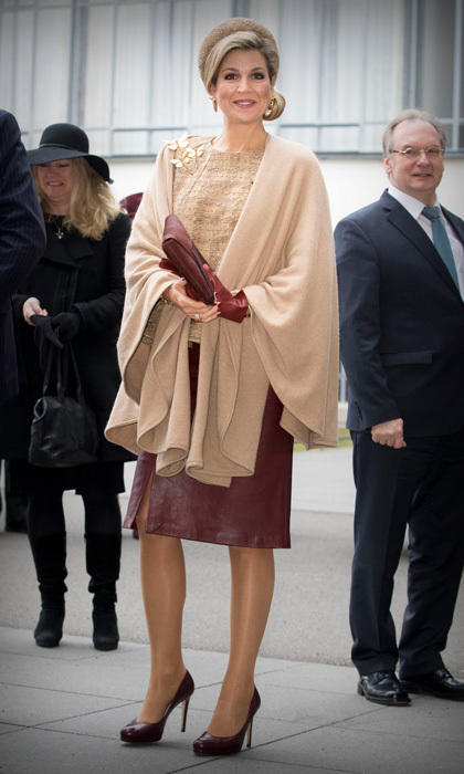 Queen Maxima kept warm in a beige wrap, which she wore over a gold top and burgundy leather skirt during her visit to the Bauhaus art academy in Dessau, Germany. 
