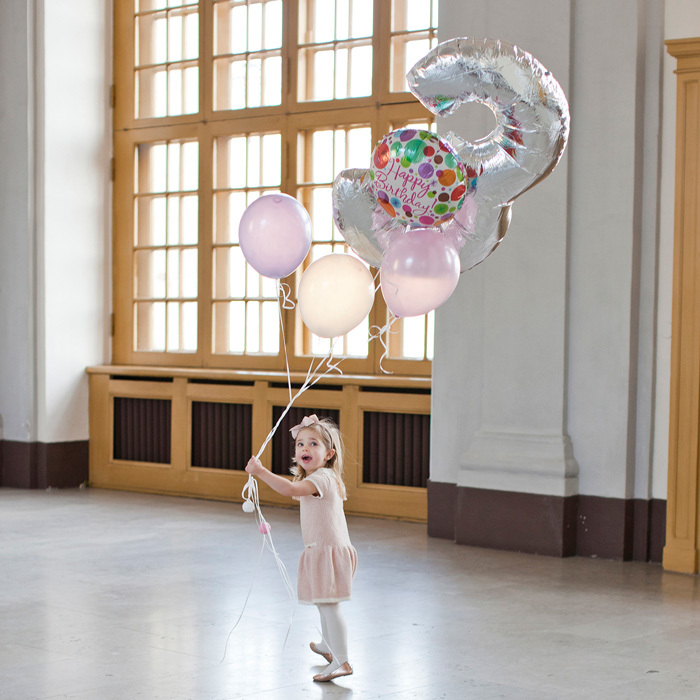 The birthday girl had fun as she strolled while holding on to a bunch of balloons. 