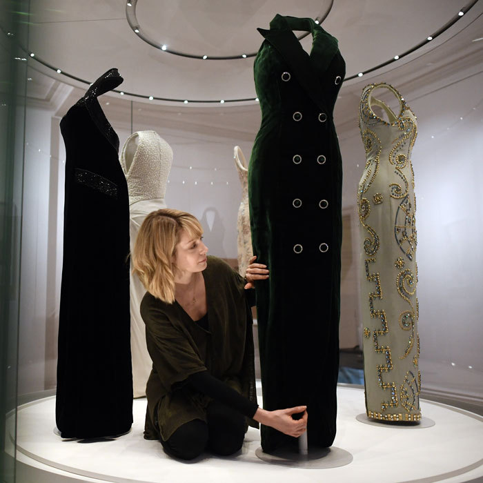 A Kensington Palace curator fixed Princess Diana's Catherine Walker dress display during a preview for the forthcoming 'Diana: Her Fashion Story' exhibit in London.