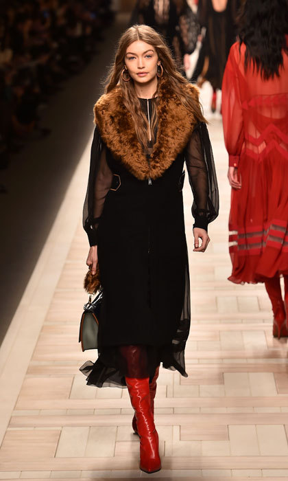 Gigi Hadid worked the runway modeling red boots and a black ensemble with fur stole at the Fendi fashion show in Milan.