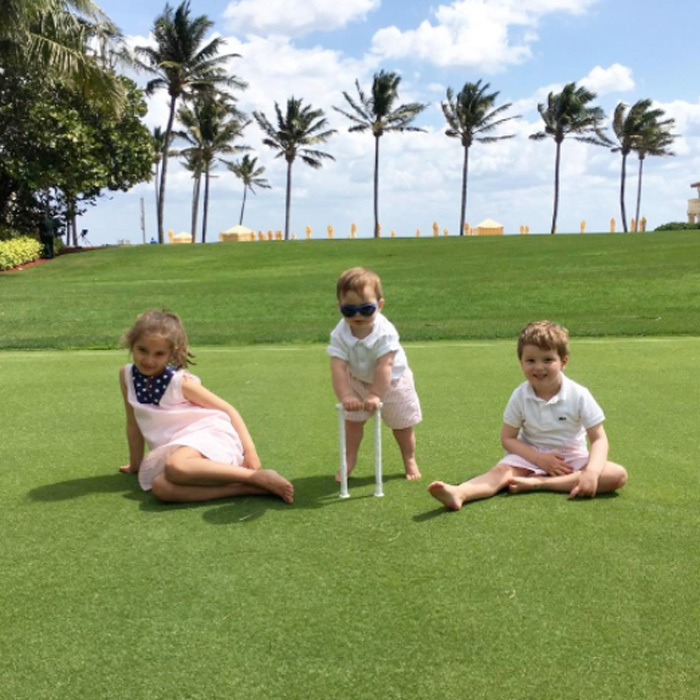 The adorable siblings were matching in red pinstripes outfits during the March weekend getaway to Mar-a-Lago. Baby Theo showed off his latest milestone hosting himself in between his older siblings in the photo snapped in Palm Beach, Florida.