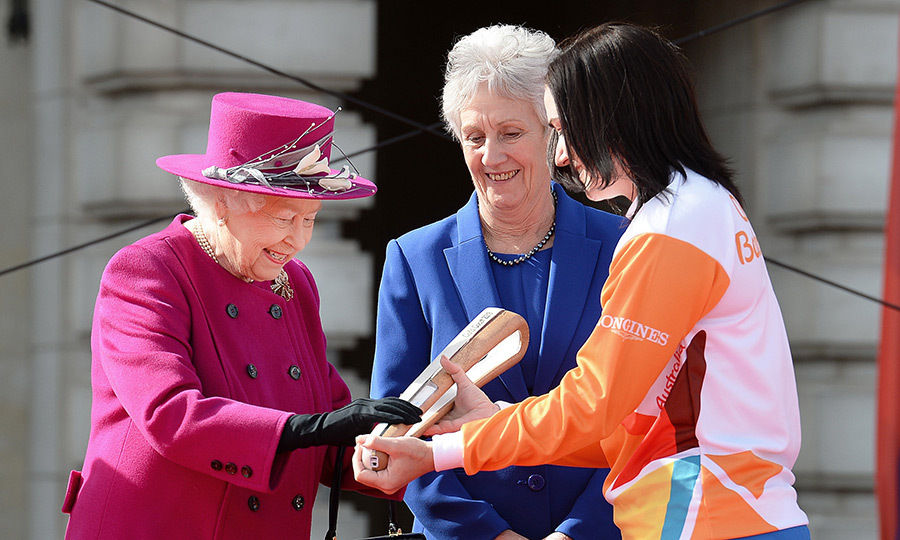 At Buckingham Palace, Australian cycling gold medalist Anna Mears passed Queen Elizabeth the relay baton as President of the Commonwealth Games Federation Louise Martin looked on. The moment took place during the launch of The Queen's Baton Relay for the XXI Commonwealth Games. 