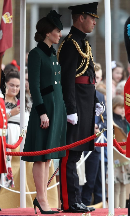 After missing the event last year, the Duchess of Cambridge returned to annual March 17 tradition on Friday, attending the Irish Guards' St Patrick's Day Parade at Household Cavalry Barracks in London at the side of husband Prince William. For the occasion, Kate wore a tailored forest green military-style coat with gold buttons and velvet trim.