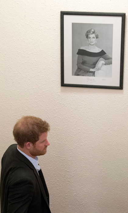 During his visit to Leicestershire Aids Support Service (LASS), Prince Harry walked by a photo of his mom Princess Diana, who visited the charity in 1991. 