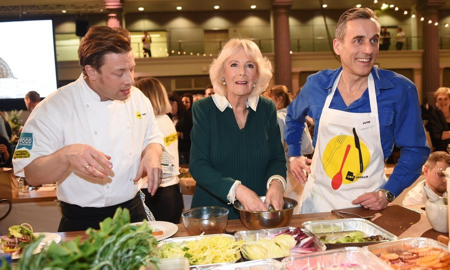 What's cookin'? Camilla, Duchess of Cornwall seemed to have the answer as she teamed up with celebrity chef Jamie Oliver, left, and CEO of Lucozade Ribena Suntory Peter Harding at the CEO Cook Off in support of UK Harvest and the Jamie Oliver Food Foundation in London on March 21.