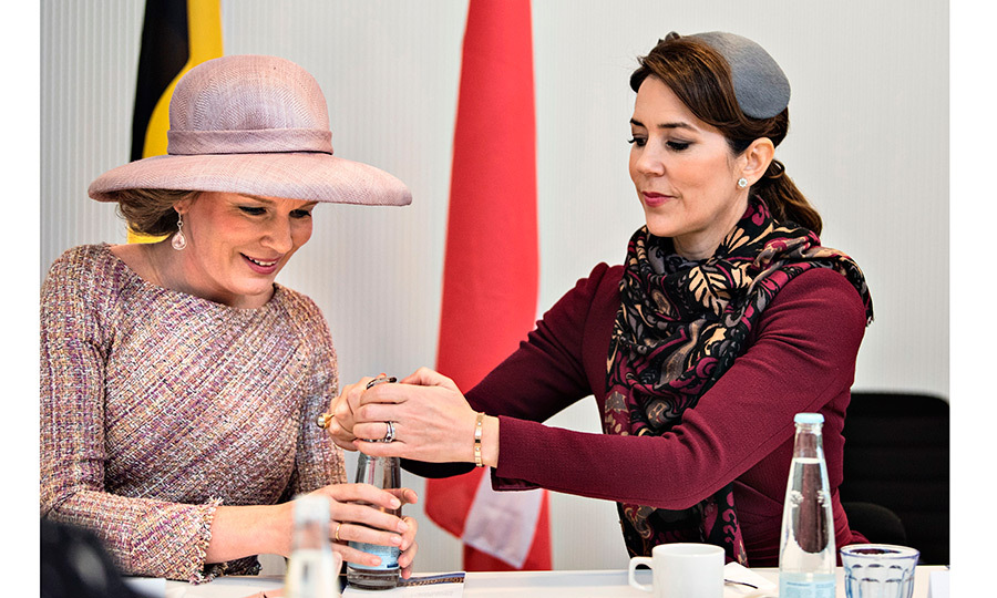 Need some help with that? Denmark's future queen, Crown Princess Mary, assisted Queen Mathilde of Belgium with a bottle cap during their meeting at the UN city in Copenhagen, Denmark, on March 29.